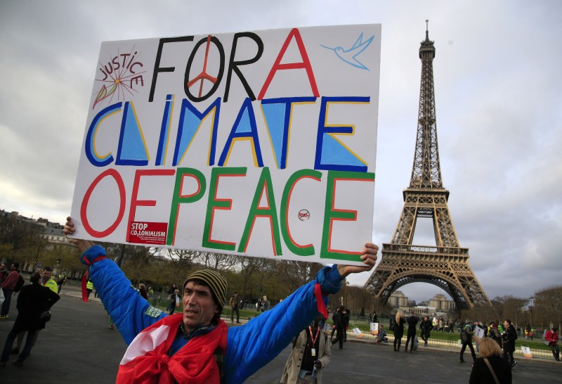 An activist hold a poster during a demonstration near the Eiffel Tower, in Paris, Saturday, Dec.12, 2015 during the COP21, the United Nations Climate Change Conference. As organizers of the Paris climate talks presented what they hope is a final draft of the accord, protesters from environmental and human rights groups gather to call attention to populations threatened by rising seas and increasing droughts and floods. (AP Photo/Thibault Camus)