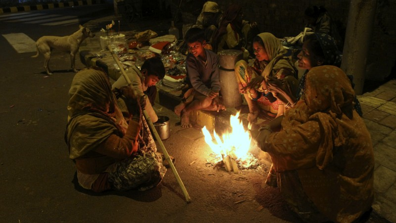 An Indian family living on a roadside keeps themselves warm by sitting around a bonfire in Ahmedabad, India, Friday, 26, 2014. Cold wave conditions continues unabated in the northern region with fog enveloping most areas and affecting transport services. (Photo: Ajit Solanki/AP)