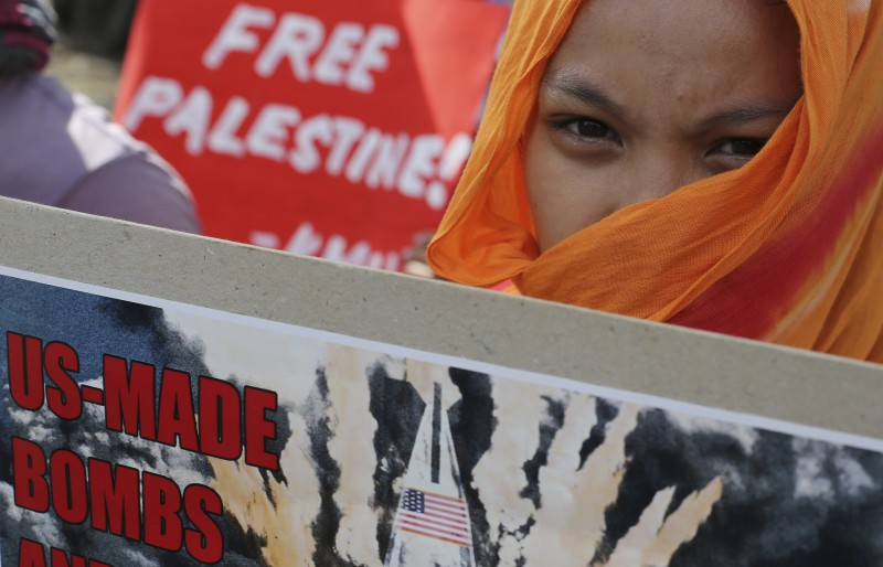 A Filipino activist holds a slogan during a rally in observance of the International Day of Solidarity with the Palestinian People in front of the U.S. Embassy in Manila, Philippines Sunday, Nov. 29, 2015. (AP Photo/Aaron Favila)