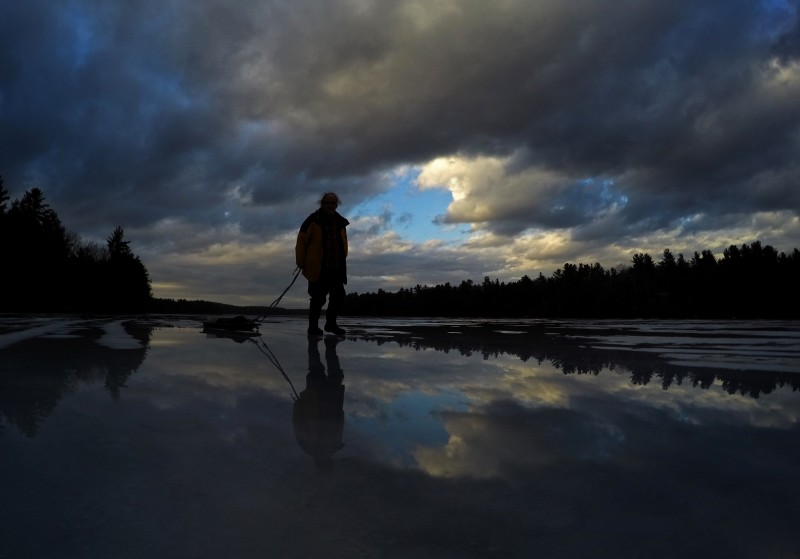 Andrew Cash heads for home after an unsuccessful afternoon of ice fishing for trout on Sabbathday Lake, Thursday, Feb. 25, 2016, in New Gloucester, Maine. Wednesday's rain storm and Thursday's temperatures in the mid-50s left a reflective layer of water on top of the ice. (AP Photo/Robert F. Bukaty)
