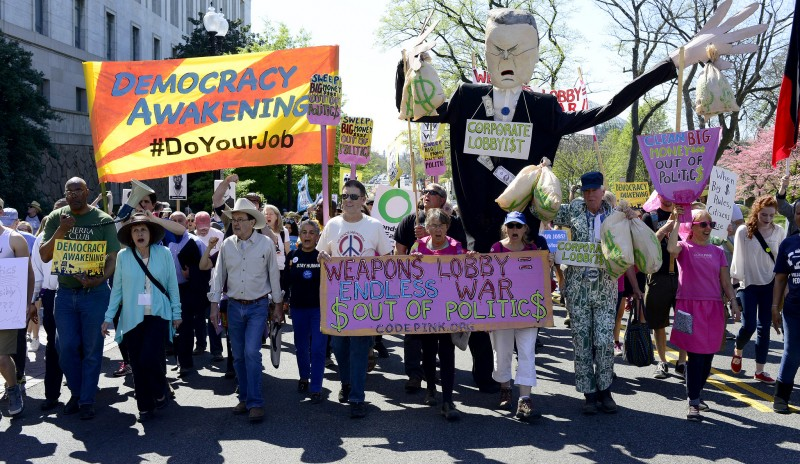Thousands gathered around the U.S. Capitol on April 17, 2016 to oppose corruption in politics. In this photo, activists carry a #DemocracyAwakening banner, a corporate lobbyist puppet, and a CODEPINK Anti-war banner. (Flickr / Stephen Melkisethian)