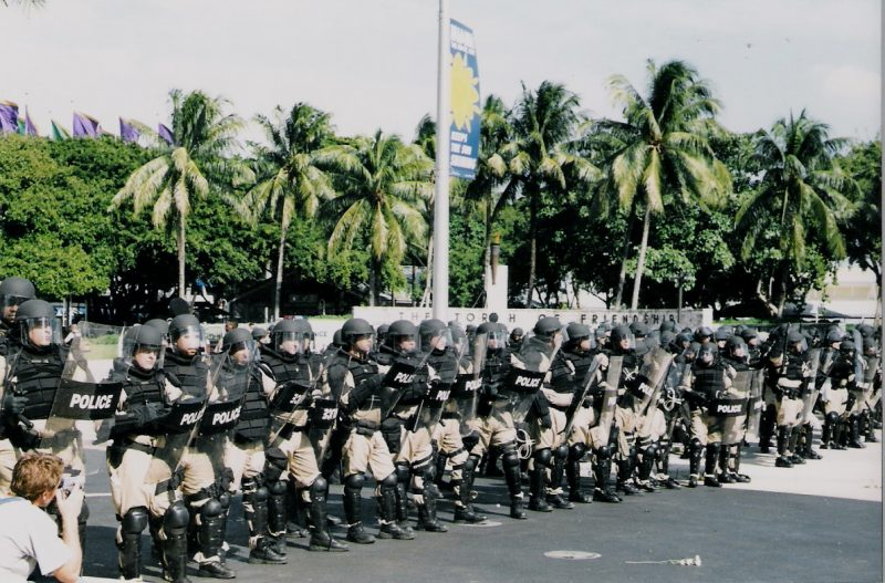 A row of armored riot police prepare to attack activists at a protest against the Free Trade Area of the Americans negotiations in Miami, Florida. (Flickr / Shooting Chris)