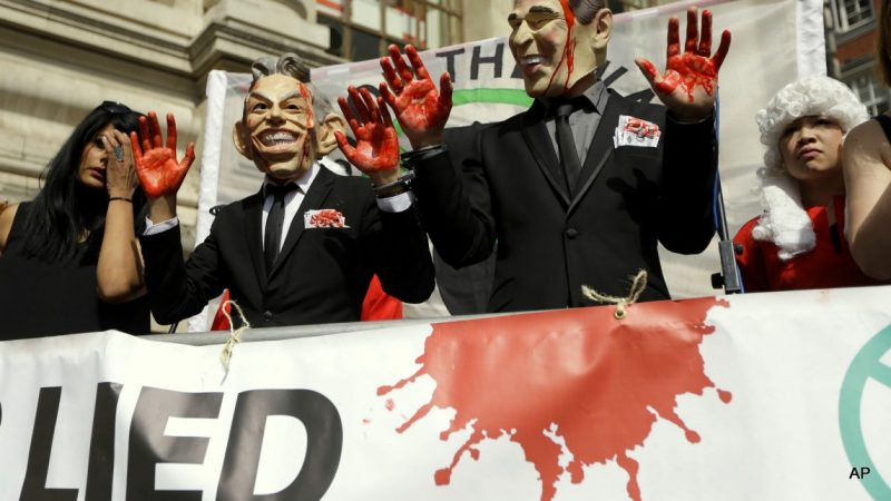 Protesters wearing a former British Prime Minister Tony Blair mask, left, and former U.S. President George W. Bush mask pose for the media outside the Queen Elizabeth II Conference Centre in London, shortly before the publication of the Chilcot report into the Iraq war, Wednesday, July 6, 2016. The long awaited British inquiry into the 2003 invasion of Iraq has been published. Led by former senior civil servant John Chilcot, the report took over seven years to prepare and runs over two million words. The report did not analyze the legality of the invasion and instead focused on the British decision-making process in the run up to the war in 2003.