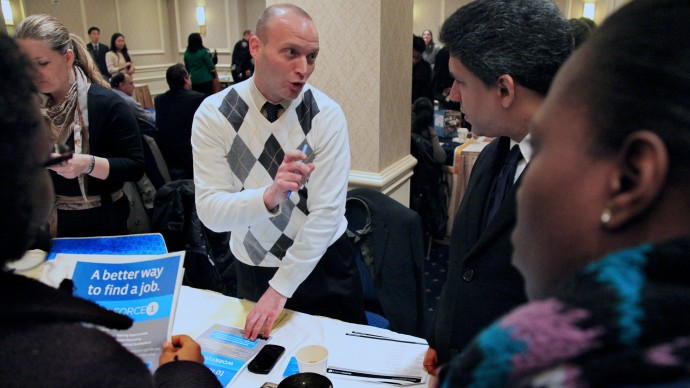 Jason Weinstein, an account manager for Workforce1 Healthcare, discusses job opportunities with attendees at JobEXPO's job fair on Wednesday, Jan. 25, 2012 in New York. (AP Photo/Bebeto Matthews)