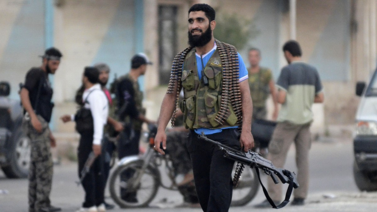 A Free Syrian Army soldier carries his weapon at the northern town of Sarmada, in Idlib province, Syria, Wednesday, Aug. 1, 2012. (AP Photo)