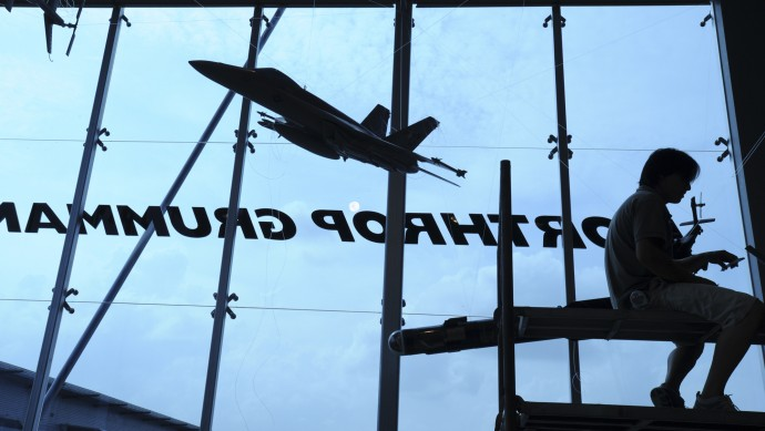 In this Feb. 15, 2008 file photo, a contractor is silhouetted while assembling model planes in the exhibition booth of Northrop Grumman at the site of the Singapore Airshow. (AP Photo/Wong Maye-E, File)