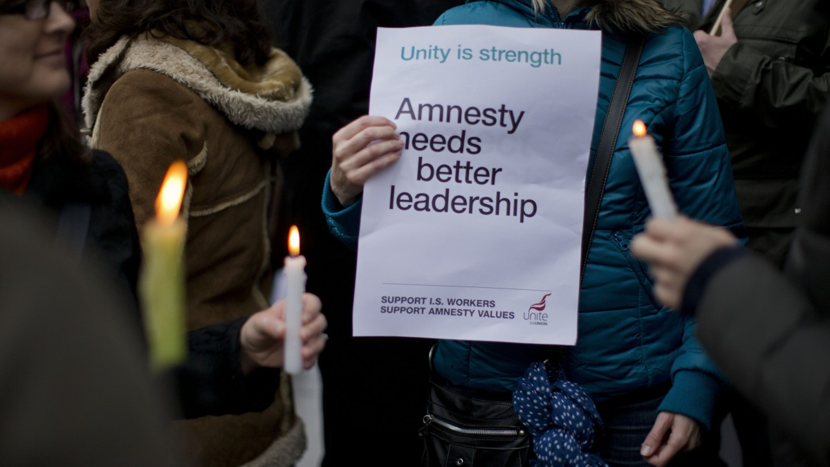People hold candles and a placard as they take part in a picket outside Amnesty International offices in London, Tuesday, Nov. 20, 2012. Amnesty International workers in London walked off the job on Tuesday as the second strike in as many months raised questions about the organization's ability to remain one of the world's pre-eminent human rights advocates. (AP Photo/Matt Dunham)