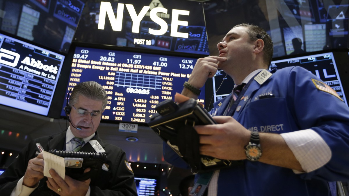 In this Wednesday, Dec. 26, 2012, photo, Daniel Kryger, left, and Kevin Lodewick Jr., right, work on the floor of the New York Stock Exchange in New York. (AP Photo/Kathy Willens)