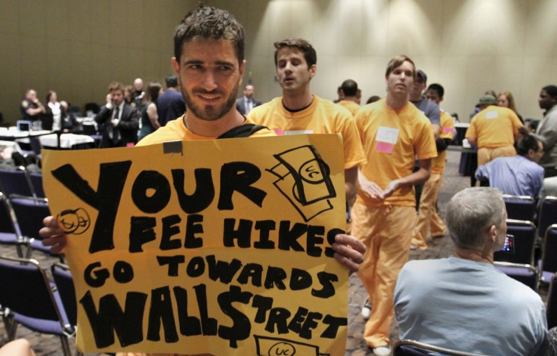 Fred Vincent, a staff researcher from the University of California, Davis,  left,  joined more than a dozen other students, staff and supporters in a march that disrupted the UC Board of Regents meeting  in Sacramento, Calif., Wednesday,  May 16, 2012.   Wearing orange and calling themselves prisoner sentenced to debt, the protestors were calling for a crackdown on UC mismanagement of executive pay, tuition hikes and police violence towards students.  No  arrests were made and the demonstrators left on their own.(AP Photo/Rich Pedroncelli)