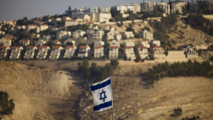 FILE - In this Monday, Sept. 7, 2009 file photo, an Israeli flag is seen in front of the West Bank Jewish settlement of Maaleh Adumim on the outskirts of Jerusalem.(AP Photo/Bernat Armangue, File)