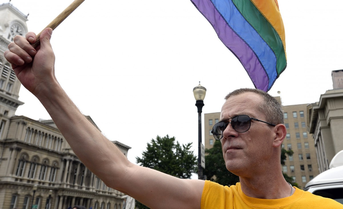 Aaron Bingham waves a rainbow flag during a rally in support of the U.S. Supreme Court decision on the Defense of Marriage Act, June 26, 2013, at Jefferson Square in Louisville, Ky. A Kentucky judge has ruled that same-sex spouses in the state still can be ordered to testify against each other because of the state's laws banning same-sex marriage. (AP Photo/Timothy D. Easley)