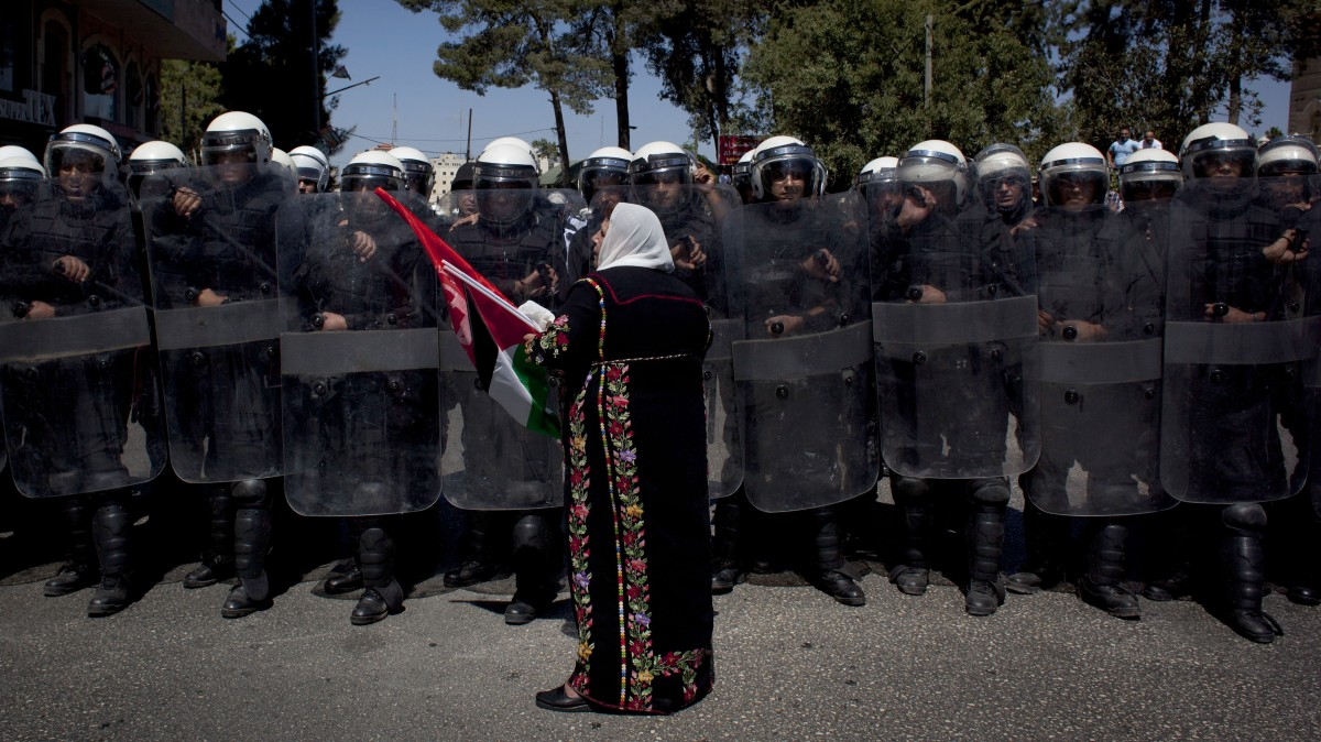 A Palestinian woman carrying national and Popular Front for the Liberation of Palestine (PFLP) flags faces Palestinian riot police blocking the road during a rally by PFLP supporters in the West Bank city of Ramallah, Saturday, Sept. 7, 2013. Hundreds of supporters of the PFLP protested against the resuming of the peace talks with Israel. (AP Photo/Nasser Nasser)