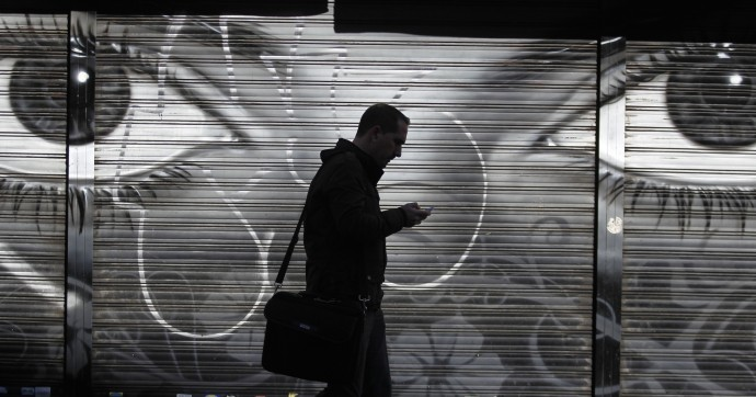 A man looks at his cell phone as he walks on the street in downtown Madrid, Thursday, Oct. 31, 2013.(AP Photo/Francisco Seco)