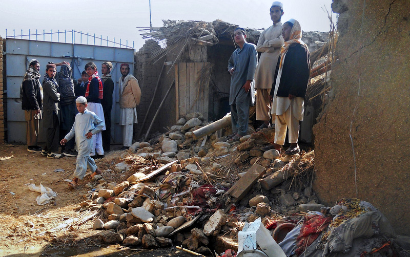 Students stand in the rubble of an Islamic seminary that was hit by a suspected U.S. drone strike