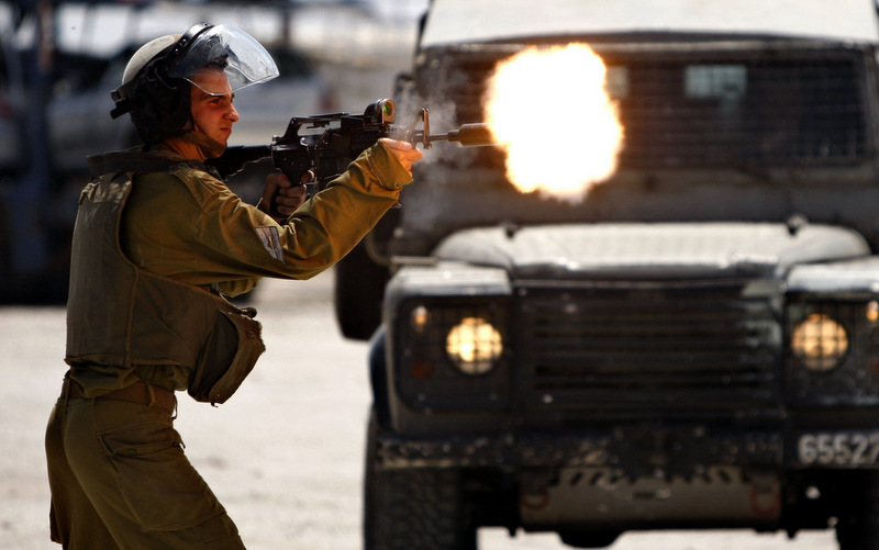 An Israeli Soldier shoots rubber bullets towards Palestinian protesters, not pictured, during a demonstration supporting prisoners in Israeli jails outside the Ofer military prison, near the West Bank city of Ramallah, Tuesday, Aug. 28, 2012. (AP Photo/Majdi Mohammed)