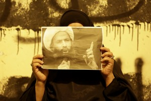 """A Bahraini anti-government protester holds up a picture of jailed Saudi Sheik Nimr al-Nimr during clashes between police and protesters in Sanabis, Bahrain, a suburb of the capital Manama, Wednesday night, Oct. 15, 2014. The well-known Shiite cleric was executed January 2, 2016 in Saudi Arabia, sparking fears of renewed unrest from his supporters in the kingdom and neighboring Bahrain. Anti-government graffiti on the wall behind her reads, """"We are steadfast and committed to our oath."""""""