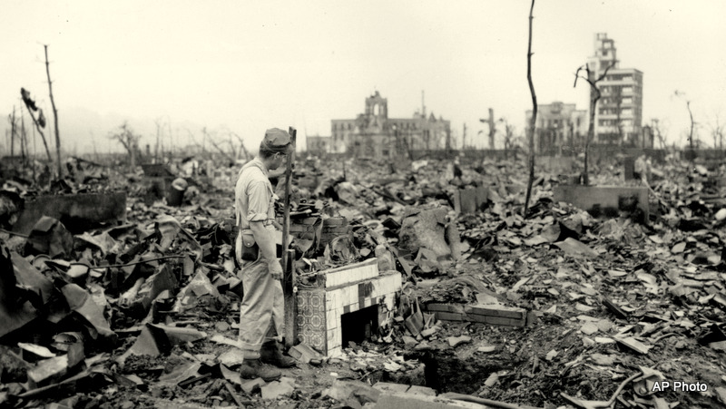 "An unidentified man stands next to a tiled fireplace where a house once stood in Hiroshima, Japan, on Sept. 7, 1945. The vast ruin is a result of ""Little Boy,"" the uranium atomic bomb detonated on Aug. 6 by the U.S."