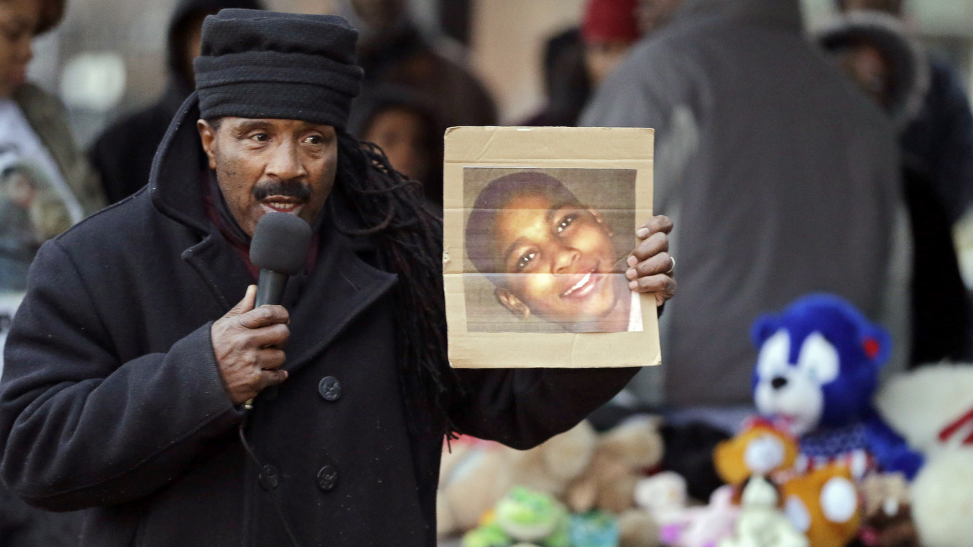 Activist Art McCoy holds a photo of Tamir Rice before a protest march at Cudell Park in Cleveland