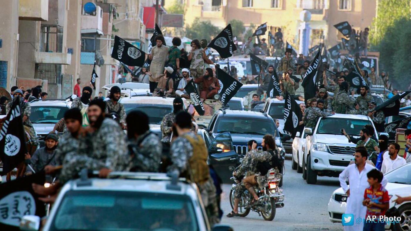 ISIS fighters parade through the streets of their de facto capital of Raqqa, Syria