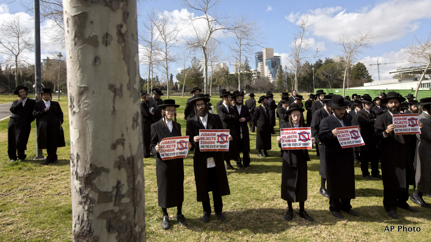 Members of the anti-Zionist ultra-Orthodox Neturei Karta group, a group that opposes Zionism and the Israeli state, hold signs during a demonstration against Prime Minister Benamin Netanyahu's U.S. visit, in front of the U.S. consulate in Jerusalem. March 3, 2015. (AP/Sebastian Scheiner)