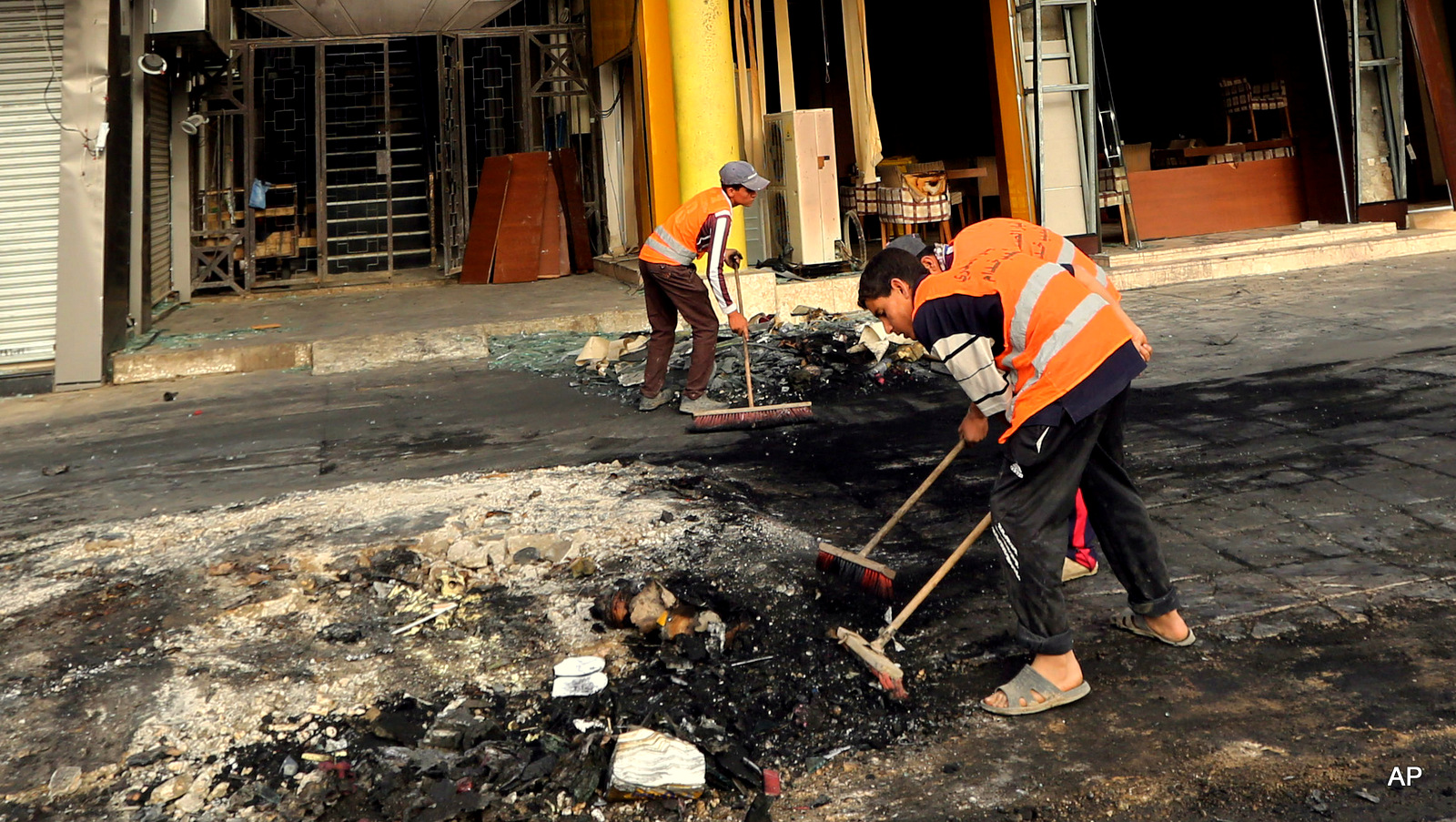 Municipality workers clean up debris in the aftermath of a car bomb explosion in Baghdad's western district of Mansour, Iraq, Tuesday, April 28, 2015. (Hadi Mizban/AP Photo)