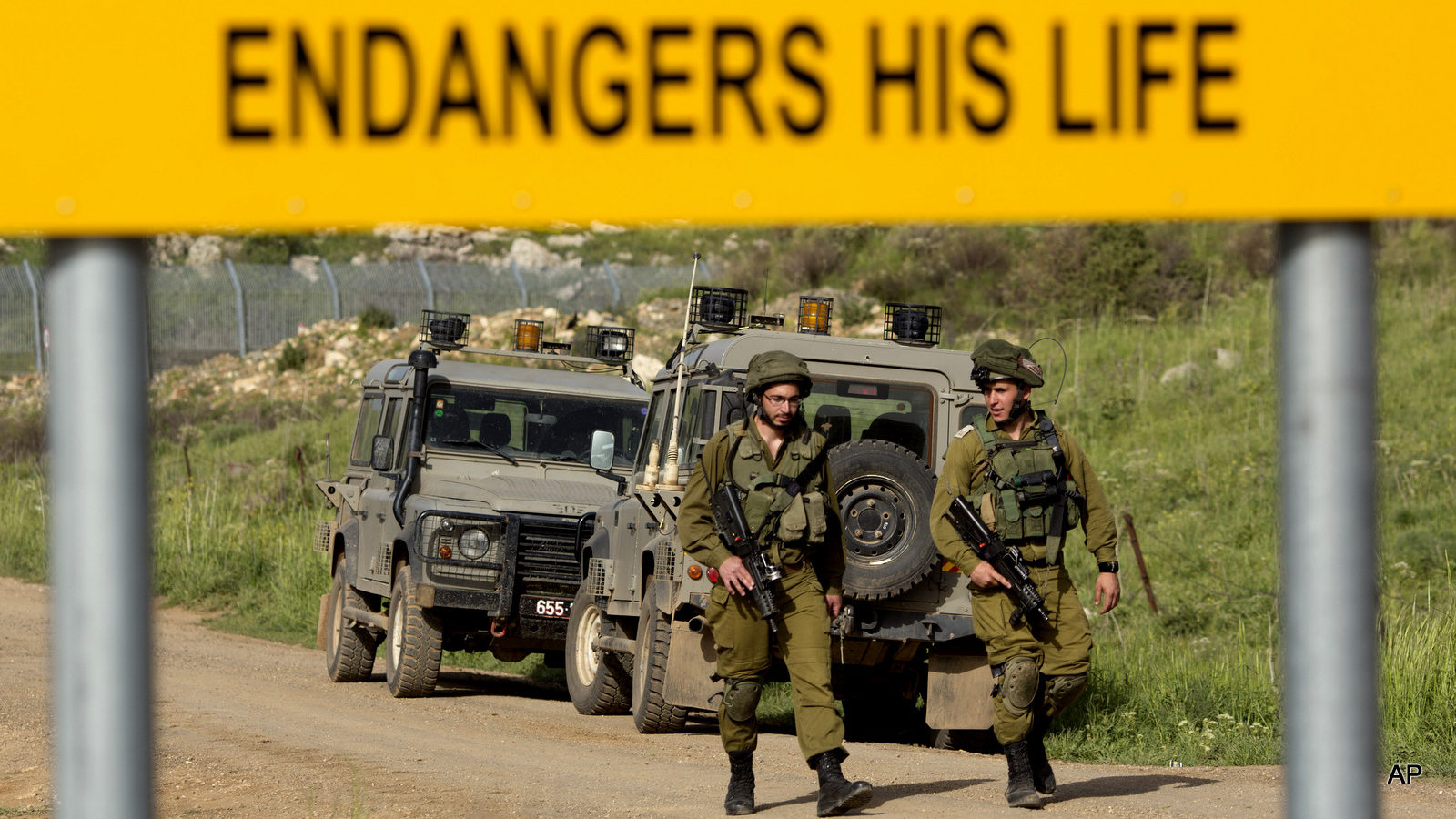 Israeli soldiers walks near the border with Syria near the site of a Sunday Israeli airstrike, in the Israeli controlled Golan Heights, Monday, April 27, 2015. Israel's military said Sunday it launched an airstrike on its border with Syria after spotting militants carrying a bomb in the Israeli-held Golan Heights. (AP Photo/Ariel Schalit)