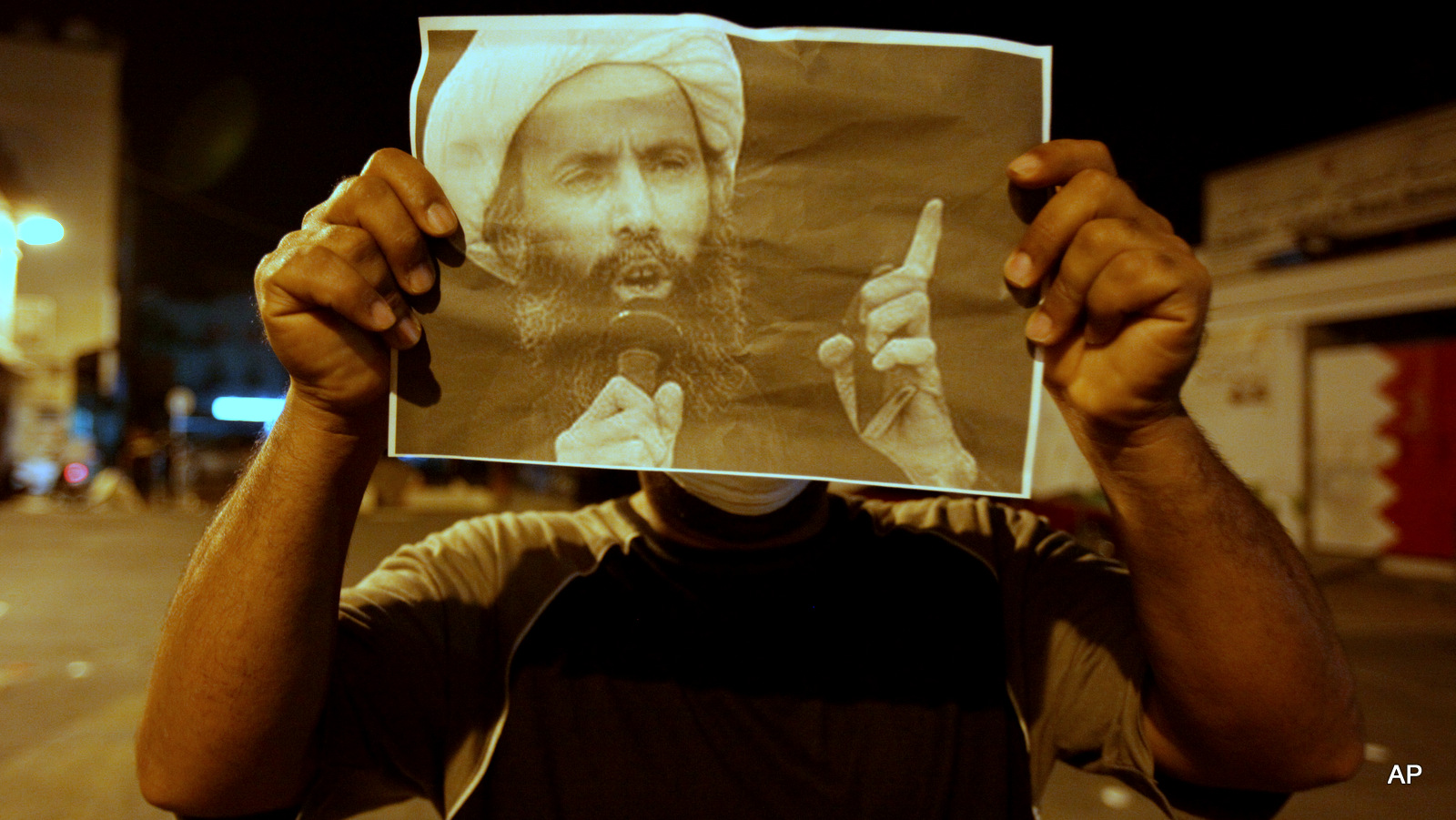 A Bahraini anti-government protester holds up a picture of jailed Saudi Sheik Nimr al-Nimr during clashes with riot police in Sanabis, Bahrain, a suburb of the capital Manama, Wednesday night, Oct. 15, 2014.  The outspoken and widely revered Shiite cleric was convicted Wednesday in Saudi Arabia of sedition and other charges and sentenced to death, raising fears of renewed unrest from his supporters in the kingdom and neighboring Bahrain.