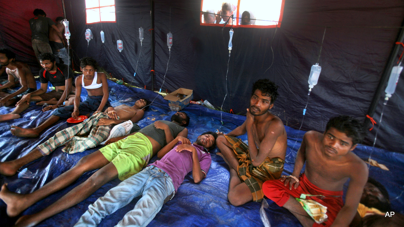 Newly arrived migrants receive medical treatment inside a makeshift tent at Kuala Langsa Port in Langsa, Aceh province, Indonesia, Friday, May 15, 2015. More than 1,000 Bangladeshi and ethnic Rohingya migrants came ashore in different parts of Indonesia and Thailand on Friday, becoming the latest refugees to slip into Southeast Asian countries that have made it clear the boat people are not welcome.
