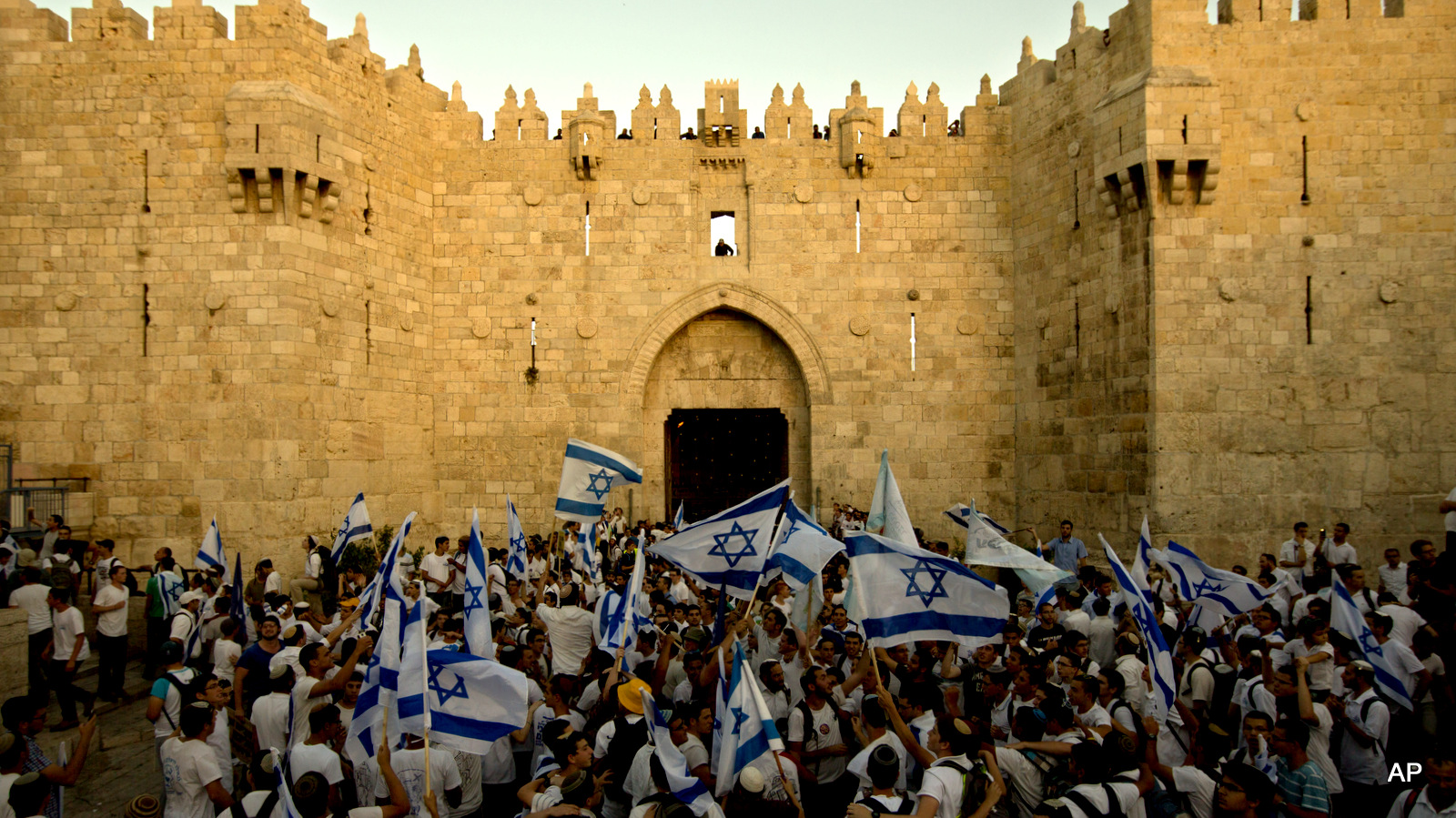 Israeli youths wave national flags as they enter Jerusalem's Old City through Damascus Gate during a march celebrating Jerusalem Day, Sunday, May 17, 2015. Under heavy police guard, thousands of Israeli demonstrators on Sunday marched through Arab sections of Jerusalem's Old City to celebrate Israel's occupation of the Palestinian land.