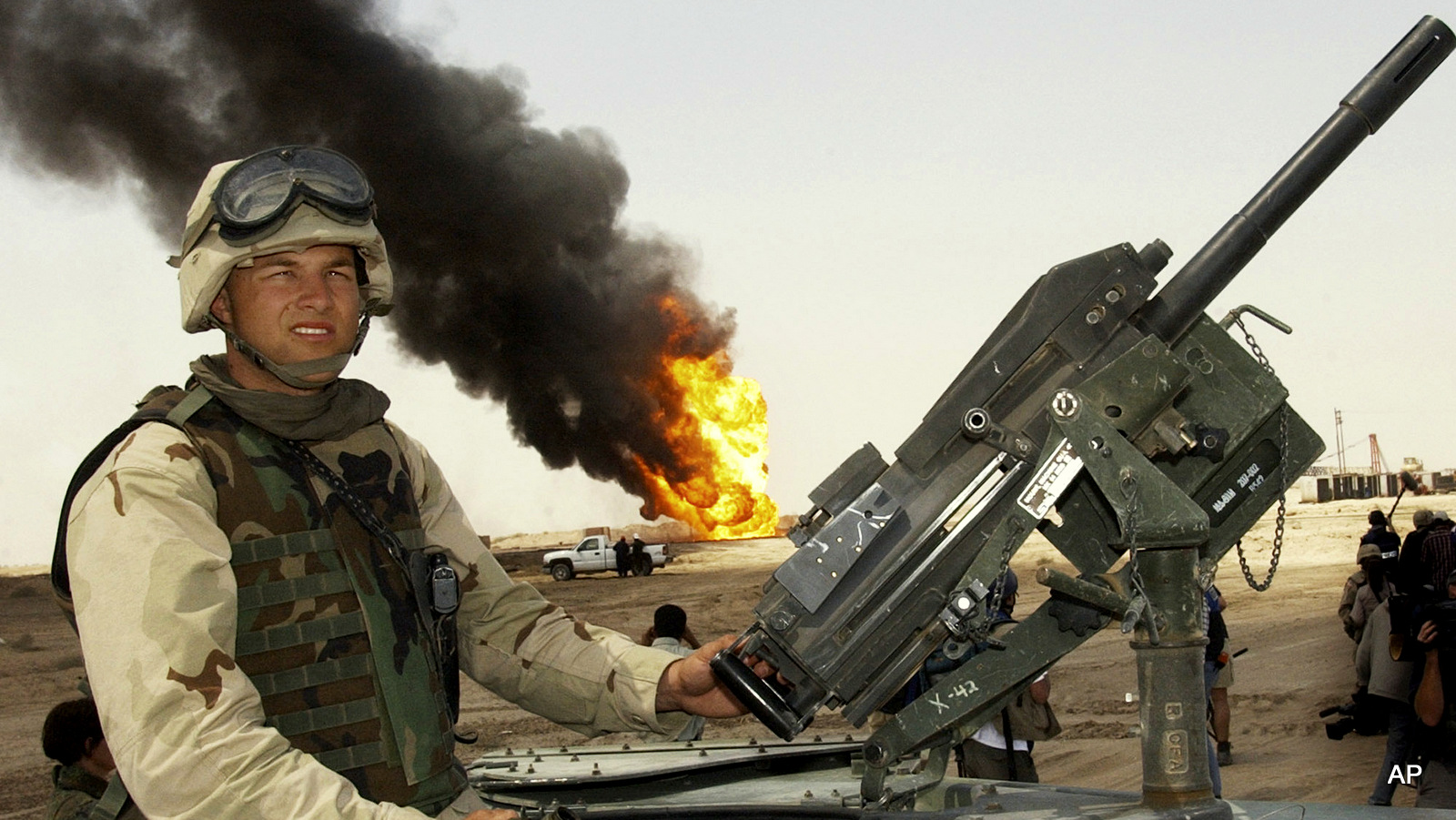 In this April 1, 2003 file photo, a U.S. soldier stands guard on top of a humvee as oil workers work on oil well fires at Rumaila oil field, southern Iraq.