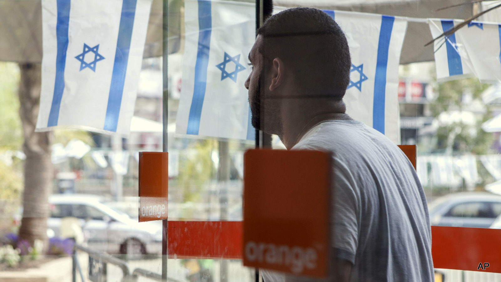 "An Israeli man walks out from the ""Partner Orange"" Communications Company's offices in the city of Rosh Haain, Israel"