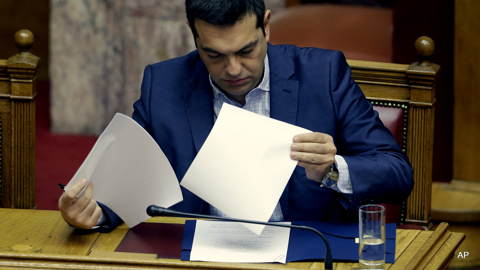 Greek Prime Minister Alexis Tsipras reads his notes as he prepares to answer opposition questions in parliament in Athens, on Friday, July 31, 2015.