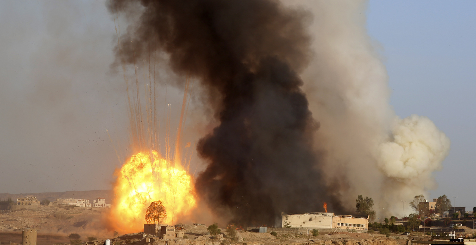 An explosion and smoke rise after an airstrike by the Saudi-led coalition in Sanaa, Yemen, Friday, Sept. 11, 2015. Saudi Arabia is leading a coalition of mainly Gulf nations fighting the Houthis, who seized the capital, Sanaa, last September. (AP Photo/Hani Mohammed)