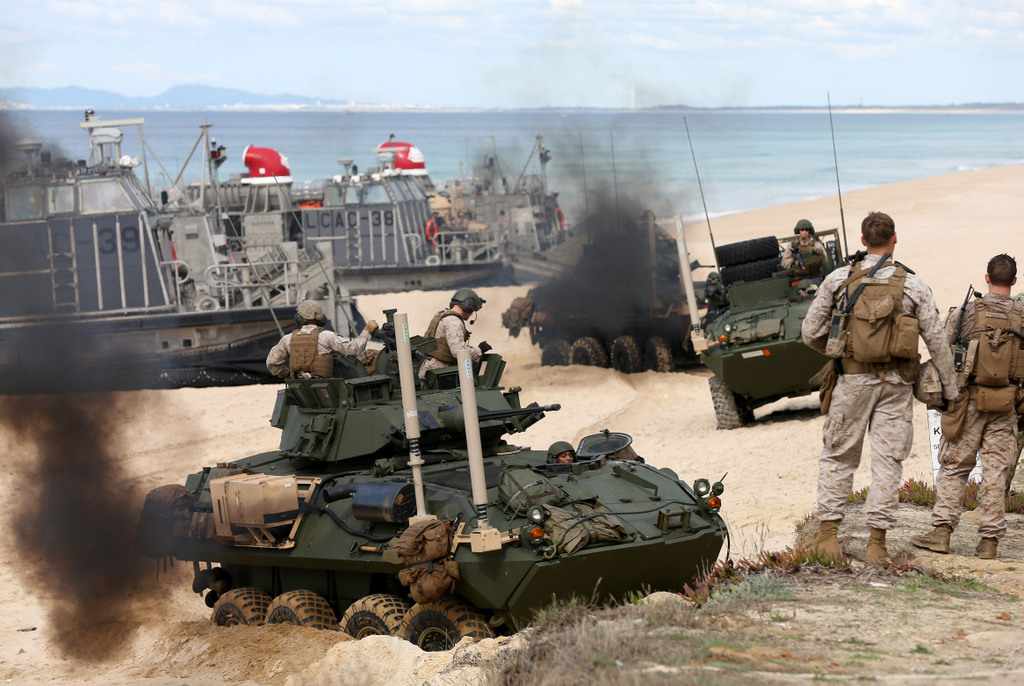 US marine armoured vehicles steers through the soft sand after getting off from a US Navy hovercraft during the NATO Trident Juncture exercise 2015 at Raposa Media beach in Pinheiro da Cruz, south of Lisbon, Tuesday, Oct. 20, 2015. NATO Allies and partner nations join forces for the next three weeks for the Alliance's Trident Juncture live military exercise involving 36,000 troops from more than 30 nations across Portugal, Italy and Spain. (AP Photo/Steven Governo)
