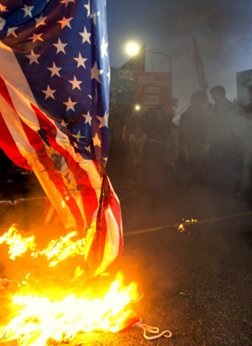 Demonstrators burn a U.S. flag in front of the U.S. embassy in Buenos Aires, Argentina. (AP/Natacha Pisarenko)
