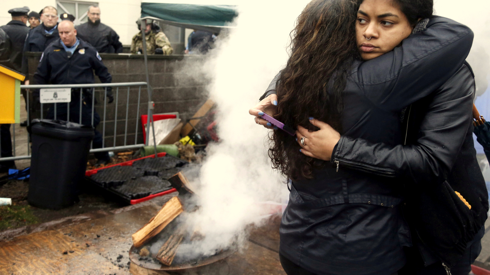 Black Lives Matter supporters embrace after Minneapolis police poured water to extinguish an encampment fire as they continued their protest, Wednesday, Nov. 18, 2015, outside the Fourth Precinct in Minneapolis. The fatal shooting of Jamar Clark, an unarmed black man by a Minneapolis police officer, has pushed racial tensions in the city's small but concentrated minority community to the fore, with the police precinct besieged by a makeshift encampment and many protesters. (AP Photo/Jim Mone)