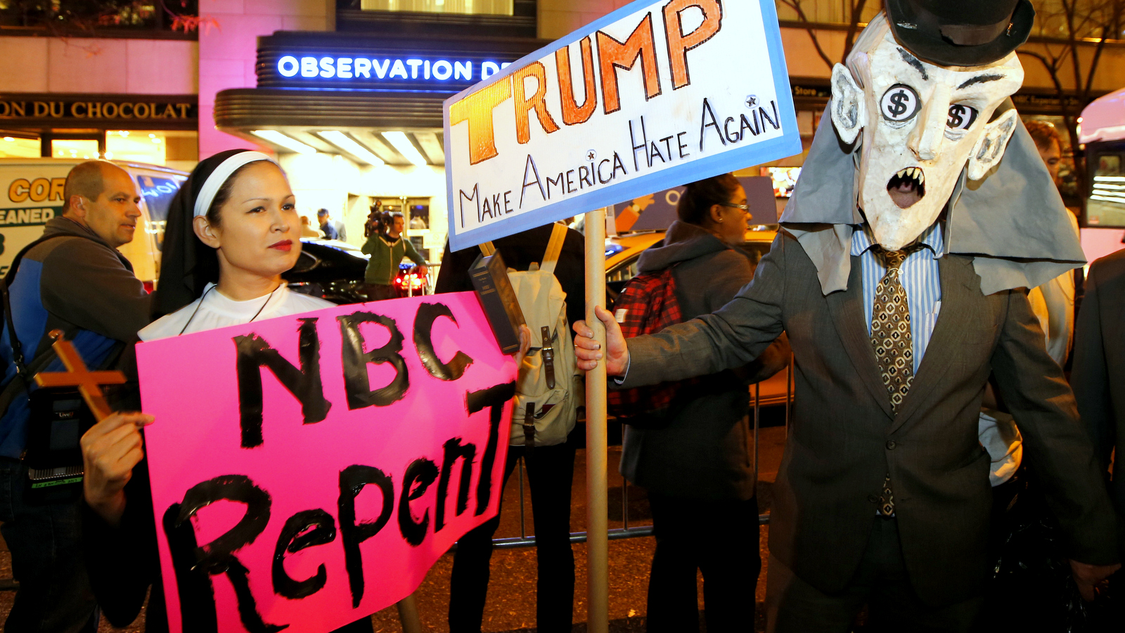 """Protesters opposed to the appearance of Republican presidential candidate Donald Trump as a guest host on this weekend's """"Saturday Night Live,"""" demonstrate in front of NBC Studios where the television show is taped and broadcast, Wednesday, Nov. 4, 2015, in New York. (AP Photo/Kathy Willens)"""