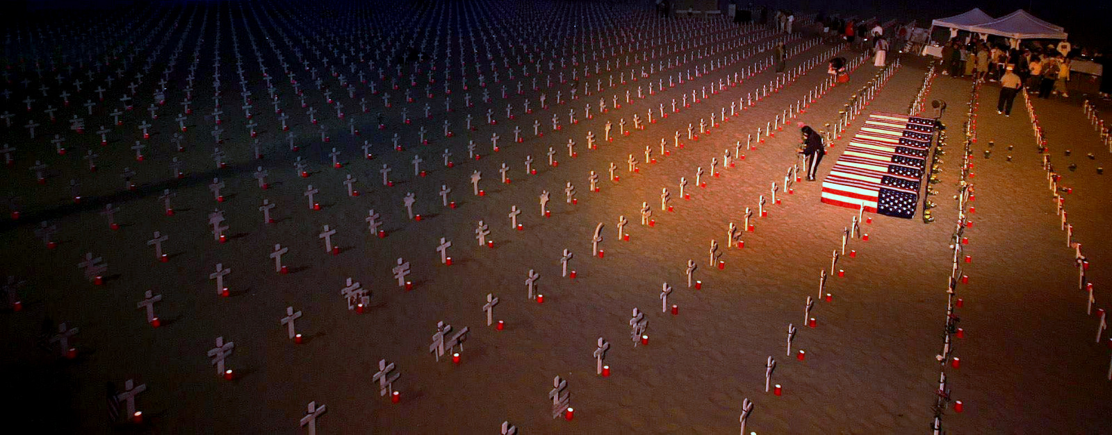 A volunteer puts flowers next to a cross at the Arlington West Iraq war memorial display on the beach next to the Santa Monica Pier in Santa Monica, Calif., on Saturday May 27, 2006. (AP Photo/Stefano Paltera)