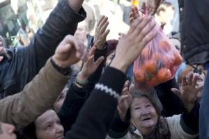 Bystanders wait to be handed bags of oranges during a free distribution of fruit and vegetables as a protest by farmers and vendors over proposed pension reforms, in Athens on Wednesday, Jan. 27, 2016. Greece's leftwing government is facing an escalating wave of protests over its proposed pension overhaul that has been demanded by bailout creditors. (AP Photo/Petros Giannakouris)