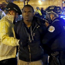 Two Chicago police officers take a man into custody during a protest march, Wednesday, Nov. 25, 2015, in Chicago, the day after murder charges were brought against police officer Jason Van Dyke in the killing of 17-year-old Laquan McDonald. (AP Photo/Charles Rex Arbogast)