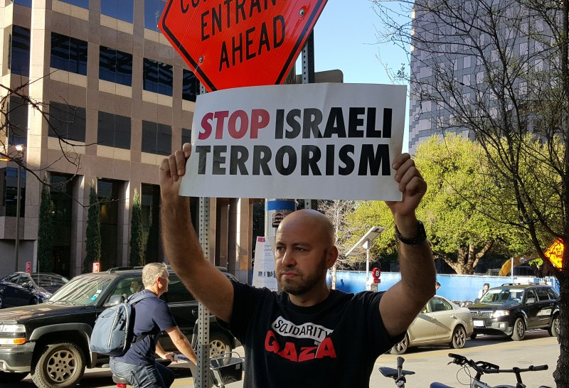 "An activist holds a ""Stop Israeli Terrorism"" sign outside the JW Marriott hotel in Austin, Texas on March 14, 2016. Jewish Voice For Peace organized the protest against the Israeli ambassador's appearance on the SXSW panel, ""Building The Perfect Country."""