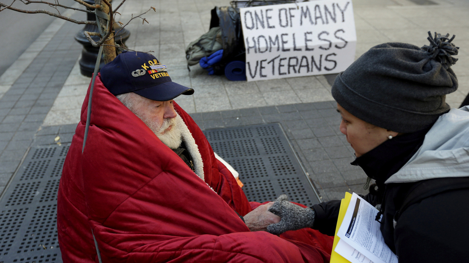 Homeless Korean War veteran Thomas Moore, 79, left, speaks with Boston Health Care for the Homeless street team outreach coordinator Romeena Lee on a sidewalk in Boston. M (AP/Steven Senne)