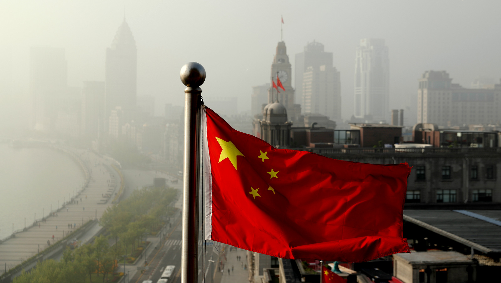 A Chinese national flag flutters against the office buildings at the Shanghai Bund shrouded by pollution and fog in Shanghai, China, Thursday, April 14, 2016. World finance officials who meet in Washington this week confront a bleak picture: Eight years after the financial crisis erupted, the global economy remains fragile and at risk of another recession. (AP Photo/Andy Wong)
