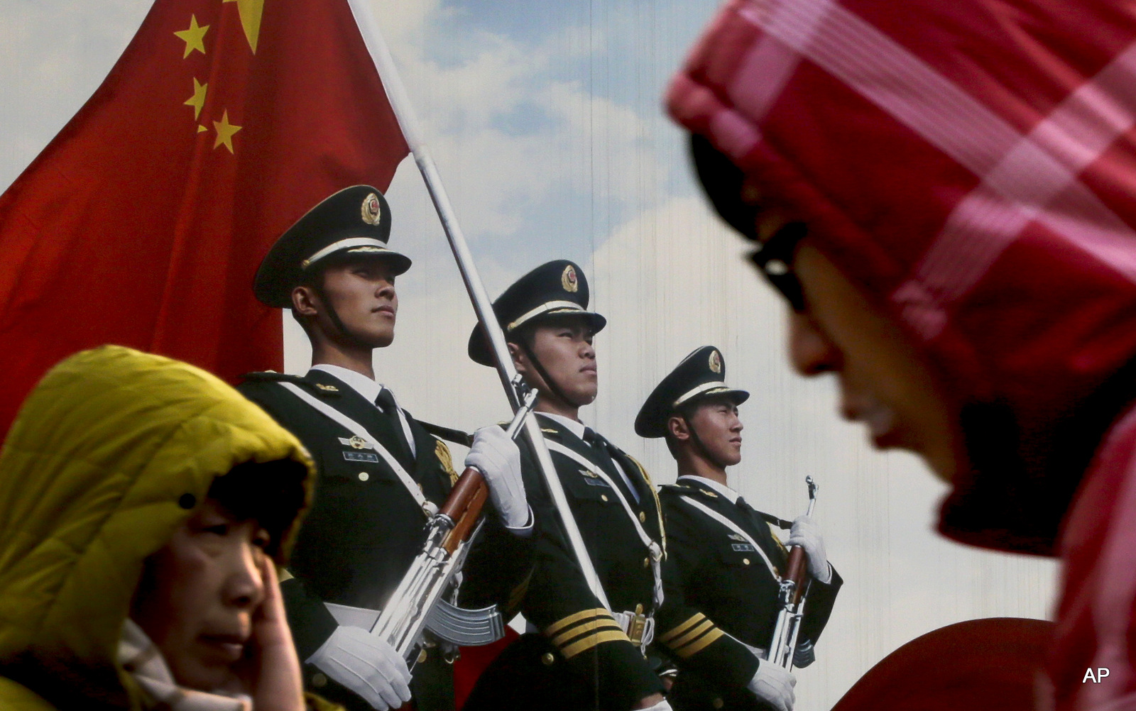 People walk past a poster of Chinese People's Liberation Army (PLA) soldiers on display in Beijing, Thursday, Jan. 21, 2016