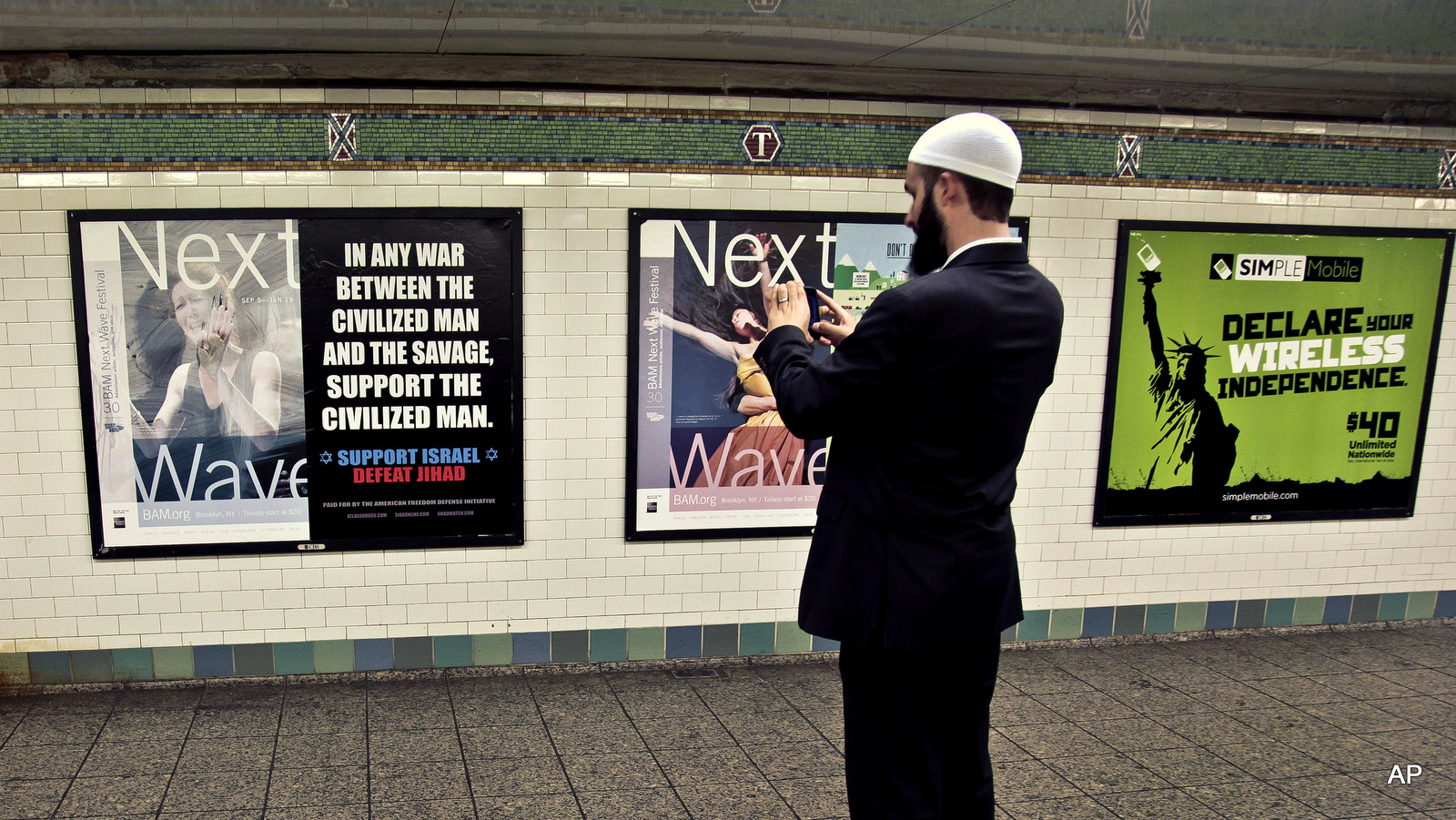 Cyrus McGoldrick, takes a photo with his cell phone of an anti-Muslim poster in New York's Times Square subway station.