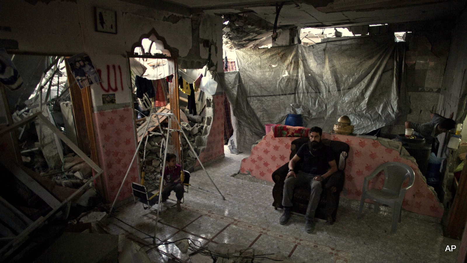 "Madi Hasanein, sits next to his son while he swings in what is left of their house in Tofah neighborhood of Gaza City. Gaza reconstruction is moving at a ""snail's pace"" and at this rate, it would likely take 30 years to rebuild the extensive damage from Israel's war on Gaza senior U.N. official said."