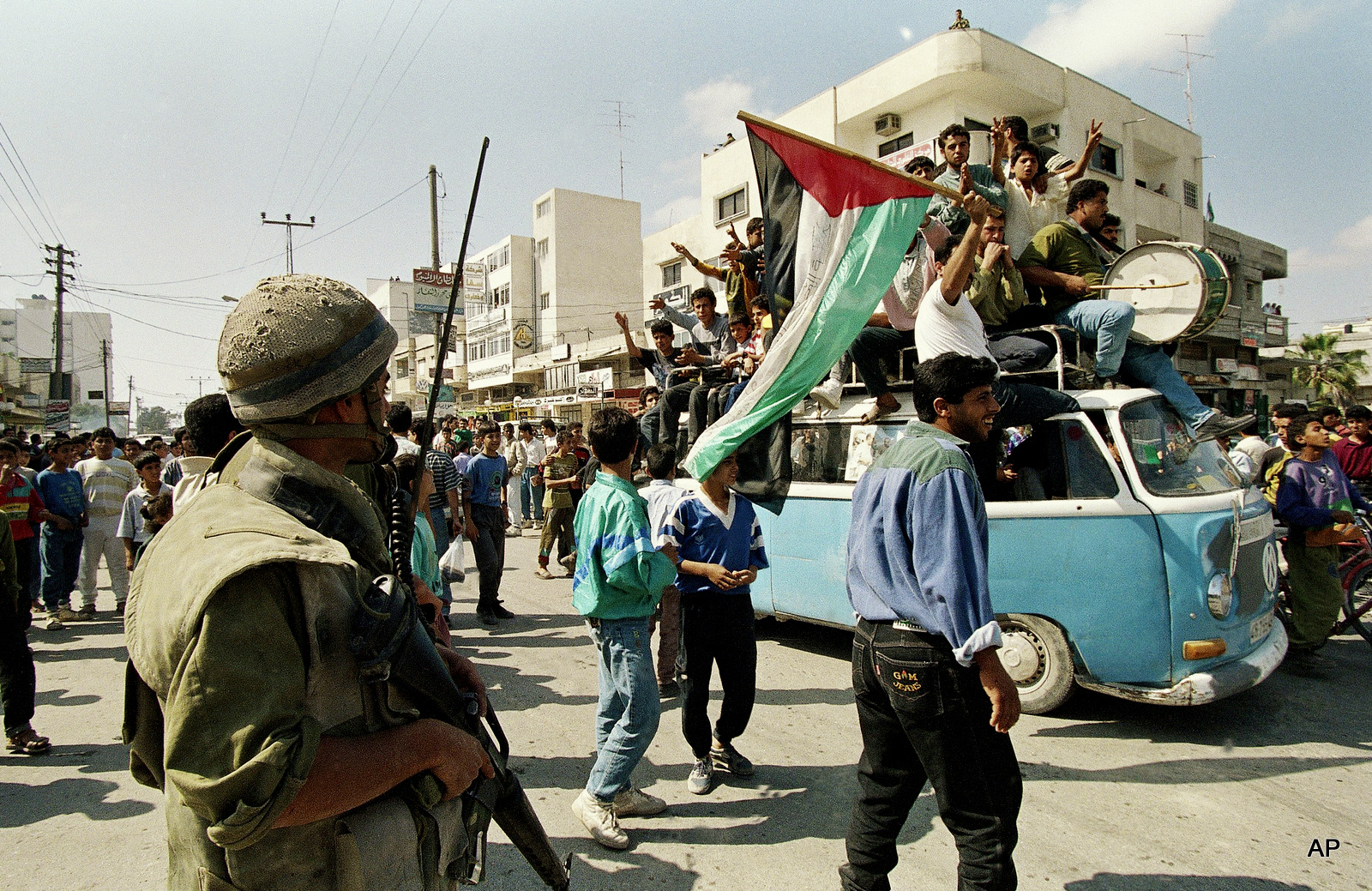 An Israeli soldier looks on as jubilant Palestinians ride on a truck celebrating the signing of the Israel-PLO agreement, May 4, 1994 in Gaza City, Gaza.