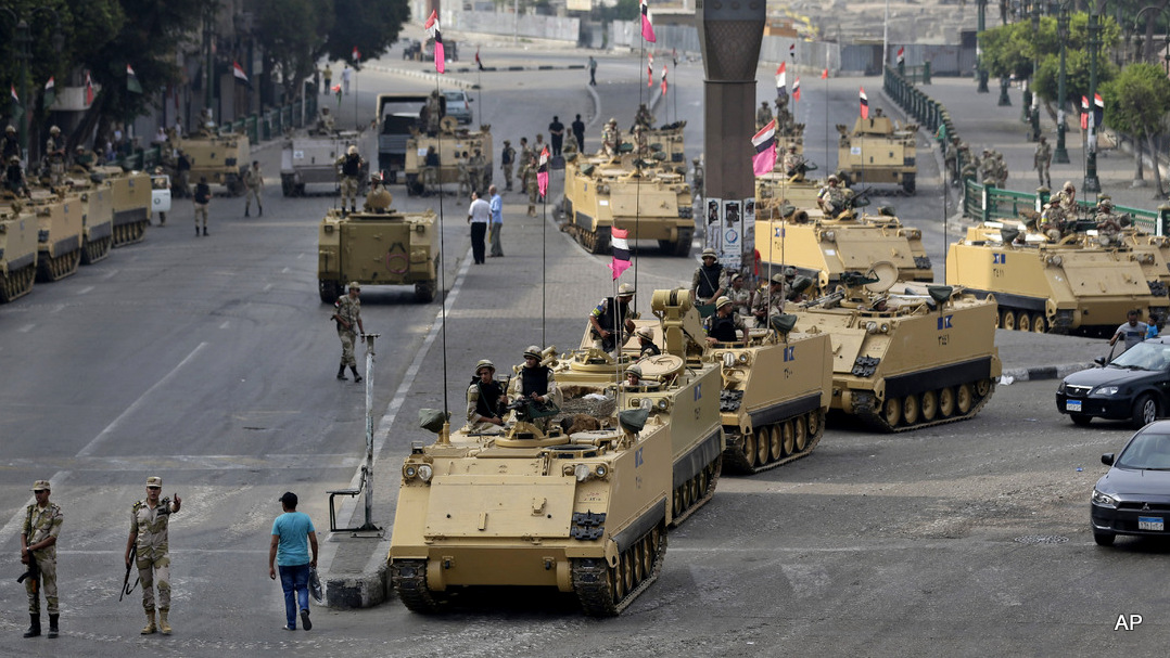 Egyptian army soldiers take their positions on top and next to their armored vehiclesin Cairo, Egypt, Friday, Aug. 16, 2013. (AP Photo/Hassan Ammar)