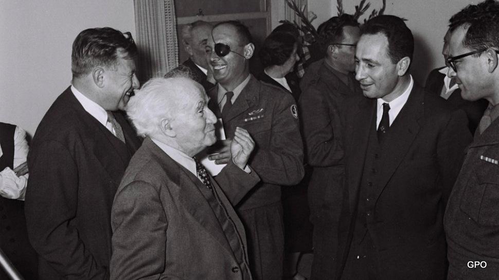 总理大卫本古里安和他的首席助手西蒙佩雷斯。背景:国防部长摩西·达扬和本·古里安的助手泰迪·科莱克。
