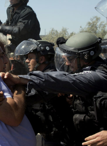 "Israeli riot police officers scuffle with Arab men in Arab village of Ara, northern Israel, Monday, Sept. 19, 2016. About 50 right wing activists protested in Ara outside the home of Nashhat Milhem, who killed three people in a shooting rampage in Tel Aviv in January 2016 before police killed him in a shootout. The demonstrators demanded Israel deport Milhem's family and shouted ""There is no Palestine."" They arrived under heavy police escort to the village, where locals held a counterdemonstration."